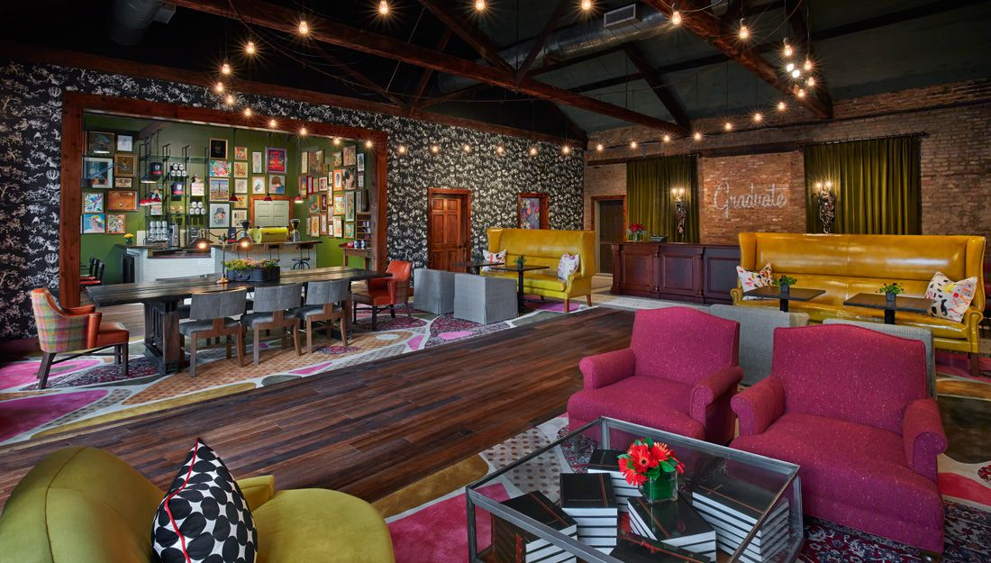 A lounge with colorful chairs, tables, and a circular chandelier hanging from the ceiling.
