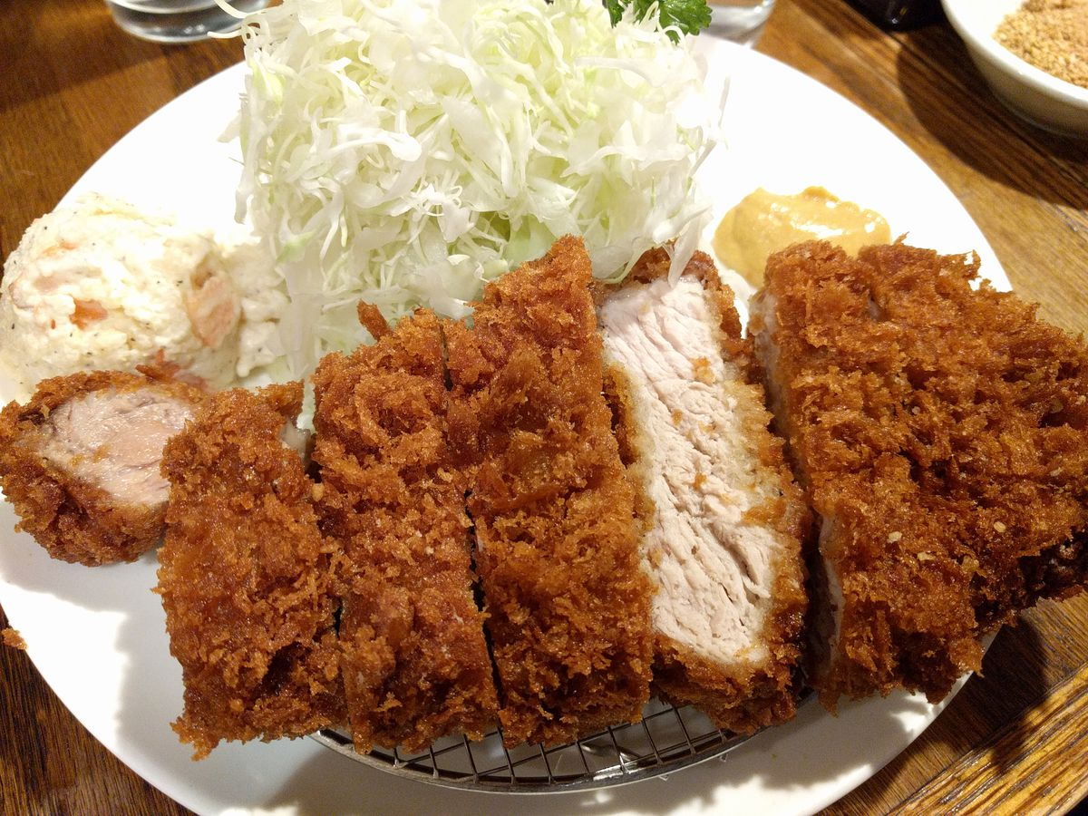 A breaded pork loin cutlet paired with shredded cabbage on a white plate