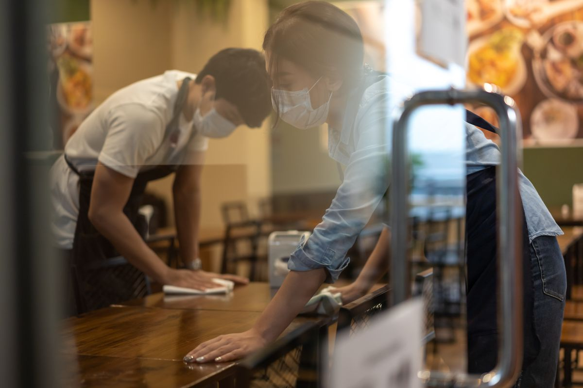 Two waiters wearing protective face mask cleans tables in a restaurant behind a window