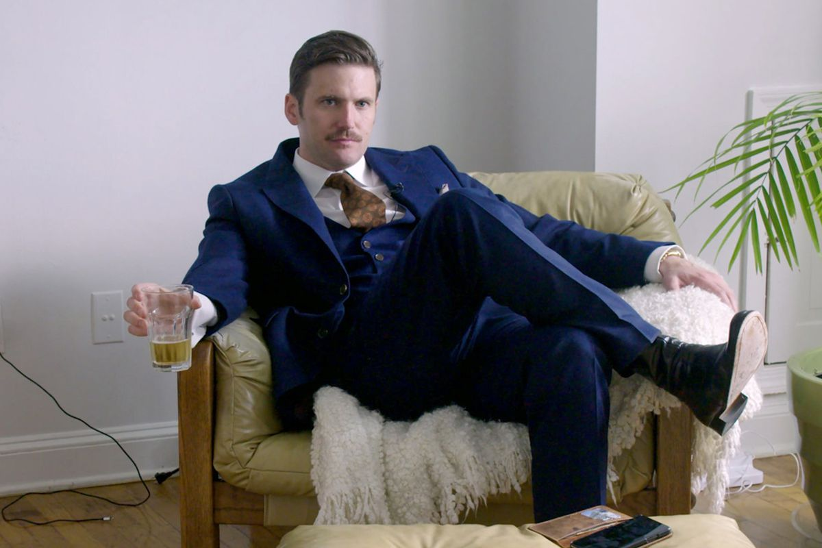 Alt-right leader Richard Spencer sits in a chair, wearing a three-piece suit and a tie.