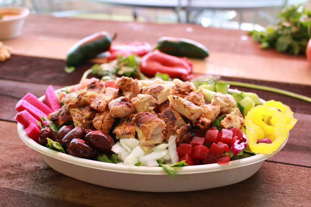 a bowl with grilled chicken, pink and bright yellow pickled veggies, kalamata olives, cubed beets, and onion