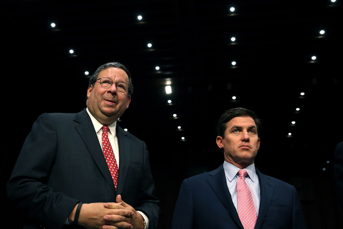 David Cohen of Comcast and Arthur Minson Jr. Time Warner Cable, wait for the start of a Senate Judiciary Commettee hearing on the proposed merger between their companies on April 9, 2014.