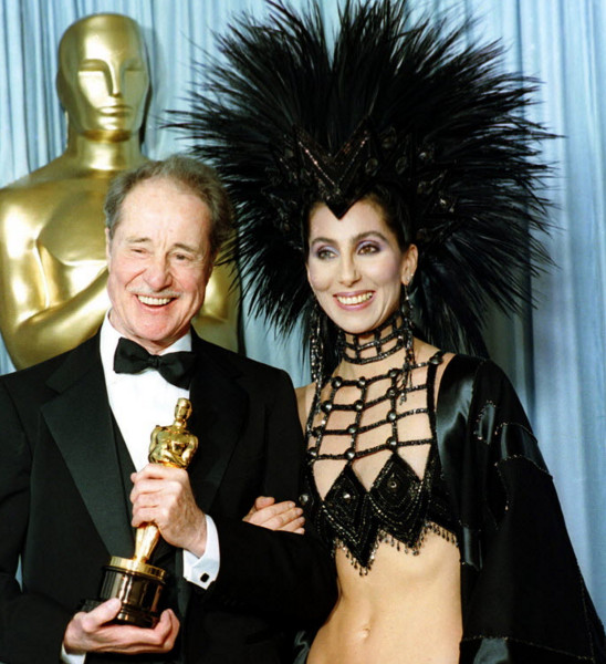 Cher, seen in one of Bob Mackie's most flamboyant creations, at the 1986 Academy Awards, where she presented Don Ameche (left) with the best supporting actor Oscar. | Lennox McClenndon/AP Photo
