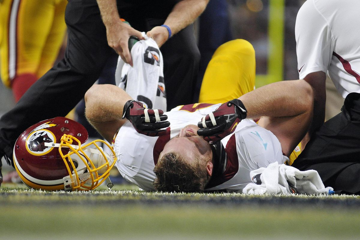 September 16, 2012; St. Louis, MO, USA; Washington Redskins defensive end Adam Carriker (94) is checked out by trainers after a play during the first half against the St. Louis Rams at the Edward Jones Dome. Mandatory Credit: Jeff Curry-US PRESSWIRE