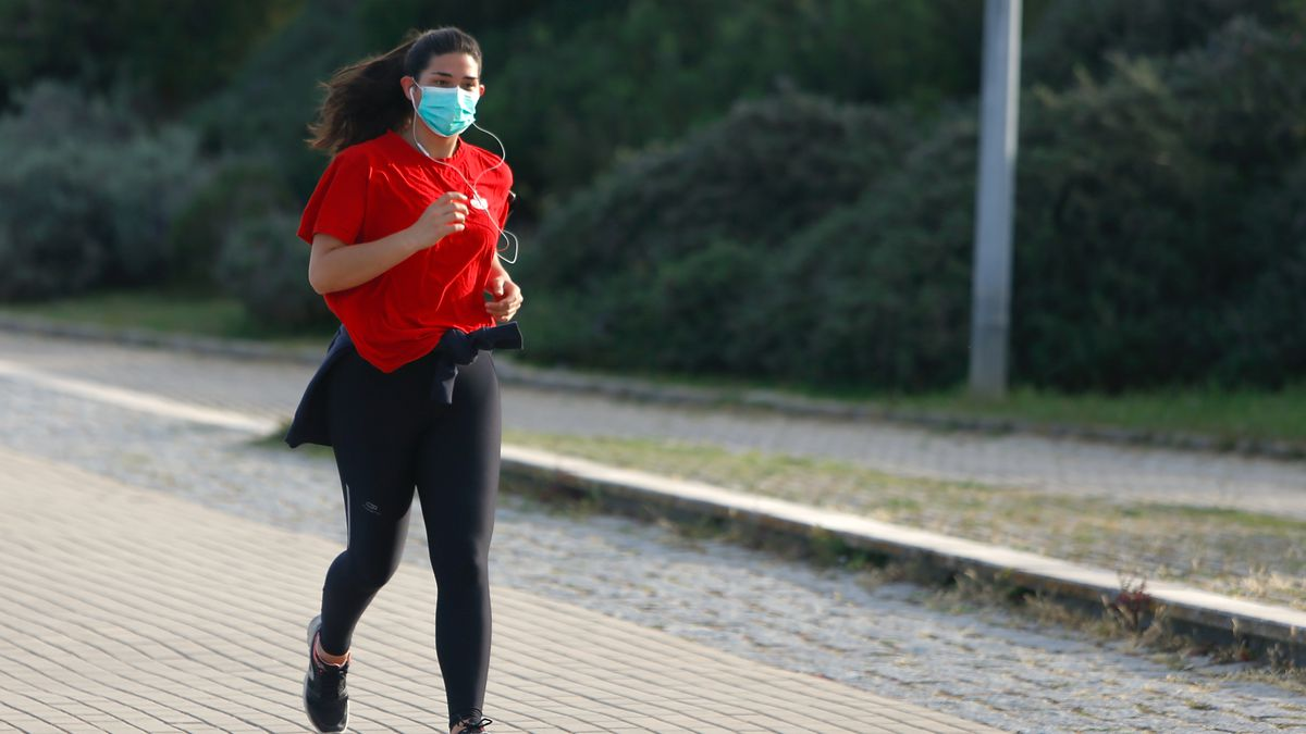 A woman running while wearing a face mask.