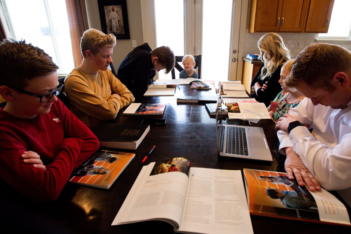 """The Kirby family, from left to right, Trevor, Jacob, Mason, Carly, Kristin, Camree and Ryan, prays before beginning a gospel study at home using """"Come, Follow Me — For Individuals and Families: Book of Mormon 2020,"""" a manual for The Church of Jesus Christ of Latter-day Saints, in Lehi on Sunday, March 15, 2020. The church temporarily canceled all meetings and activities worldwide to limit public gatherings in response to the coronavirus pandemic."""