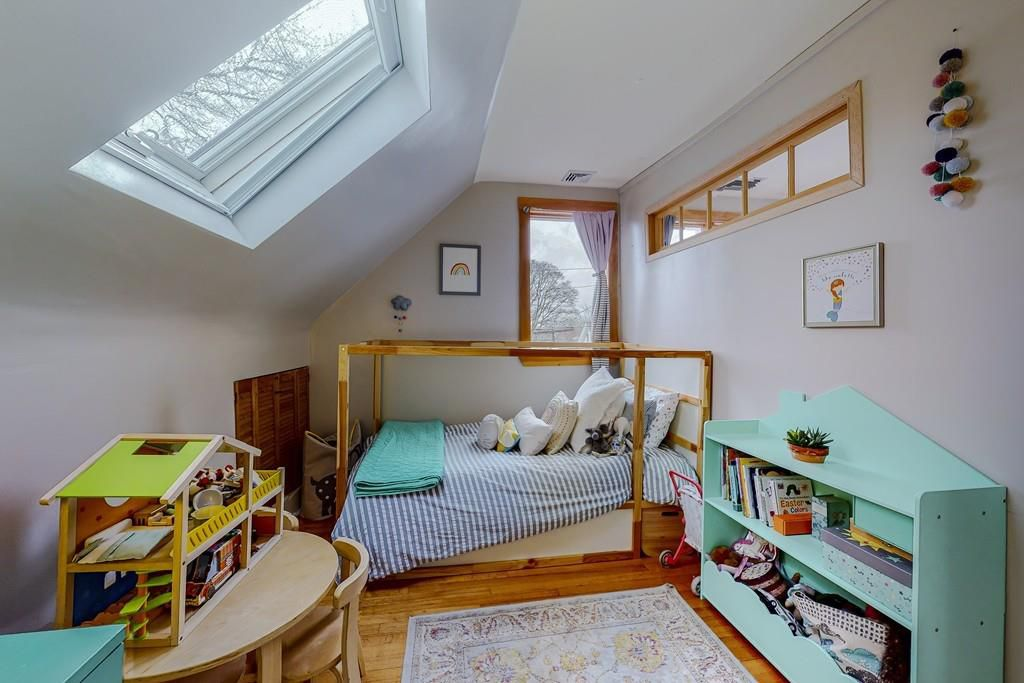 A narrow bedroom with a bed beneath a skylight on a sloping ceiling.