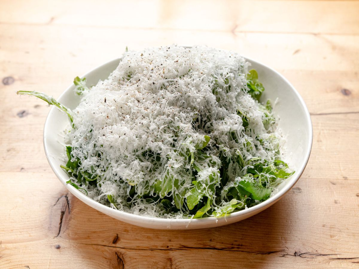 A bed of arugula is topped with a mountain of parmesan cheese in a white bowl