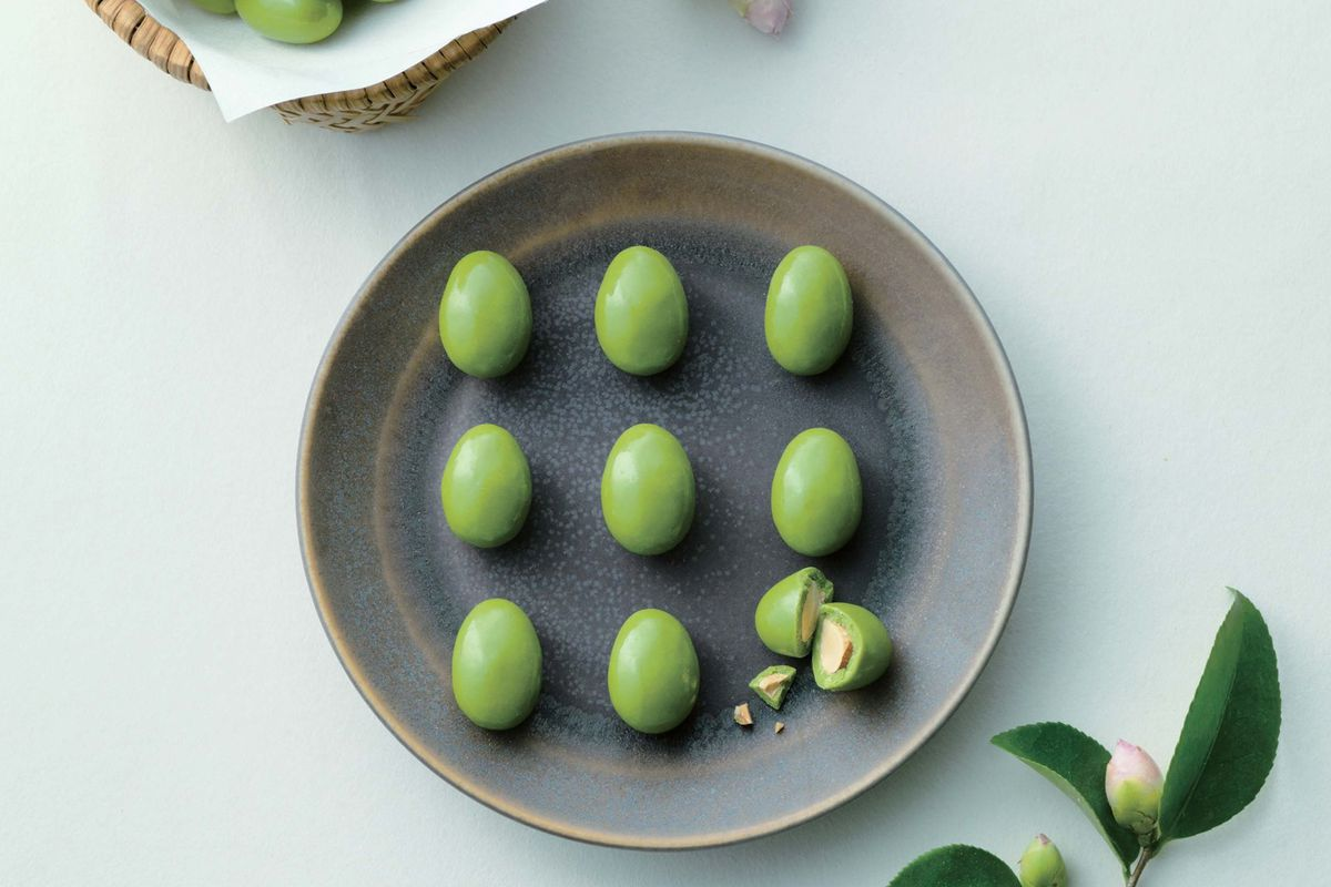 a plate of almonds covered in bright green chocolate flavored like matcha tea