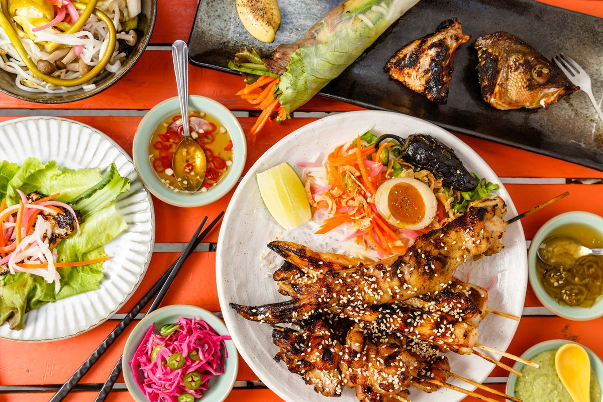 A spread of dishes at Falansai, including chicken skewers, a fish head, a beef spring roll, and assorted condiments