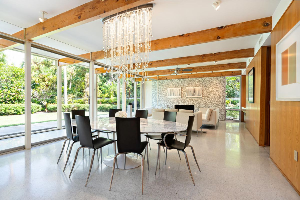 A dining room features a round table with black chairs underneath a waterfall chandelier.