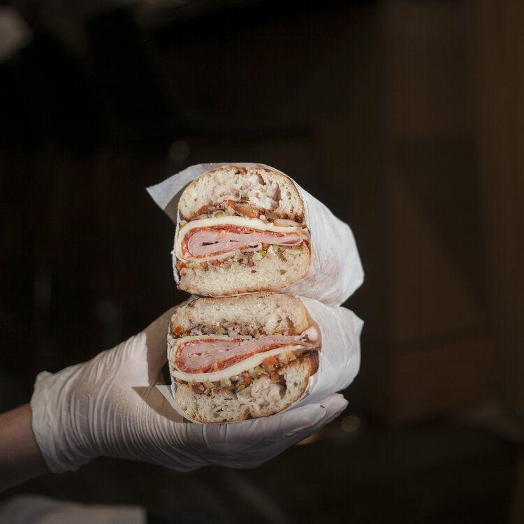 Photo of gloved hand holding massive dinner sandwich