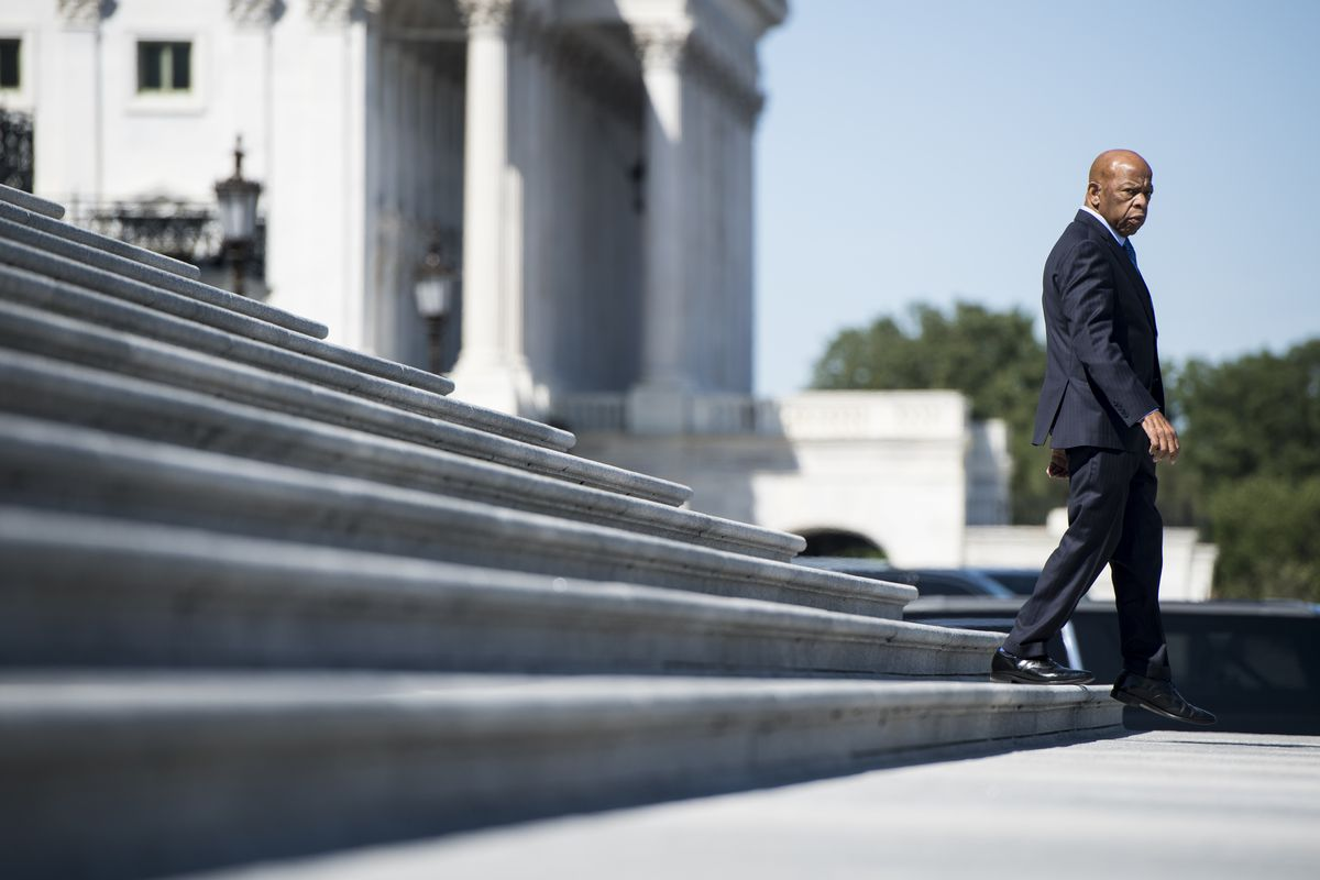 Lewis, his head cleanly shaven, and a serious expression on his face, walks down the sweeping white steps of the Capitol in a tailored navy suit.