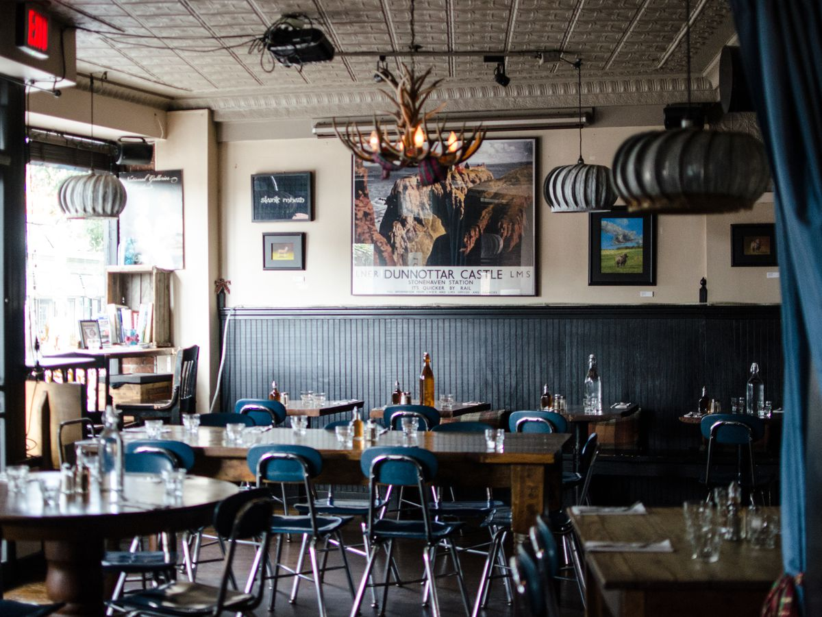 Interior of the Haven, a Scottish restaurant in Boston's Jamaica Plain, featuring an antler chandelier and simple tables and chairs.