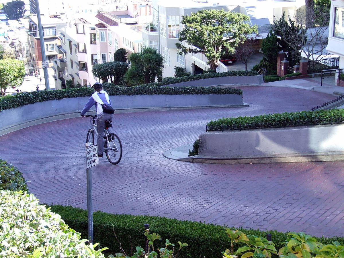 A cyclist rides their bike down a winding path on Lombard Street in San Francisco. There are many city buildings in the distance.