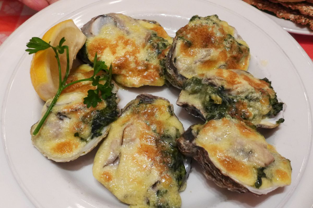 A half dozen oysters on the half shell covered with cream sauce and spinach...