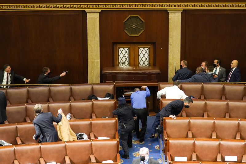Lawmakers and aides duck and scramble for cover, diving inside the rows of chairs members usually sit in. One man in a black suit raises a gun. The doors of the chamber have been barricaded with what appears to be a wooden desk.