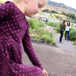 Lily Munson, 4, plays in a dirt pile while her mother, Maryann, and Lisa Boone chat after the dedication of the Popperton Plots community garden in Salt Lake City on Friday, Aug. 22, 2014.