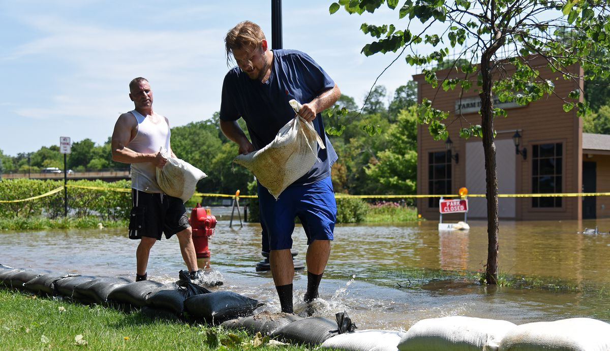 Tom McCleary, right, and Ray Robarge put another layer of sandbags on their way after Wednesday night's rain raised the water level to a new high point for the week on La Fox River Drive Thursday.   Rick West/Daily Herald