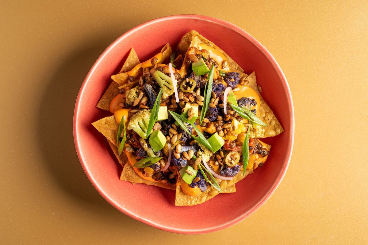 Vegetable nachos with smoked lentil chili and cashew cheese sauce in a pink bowl.