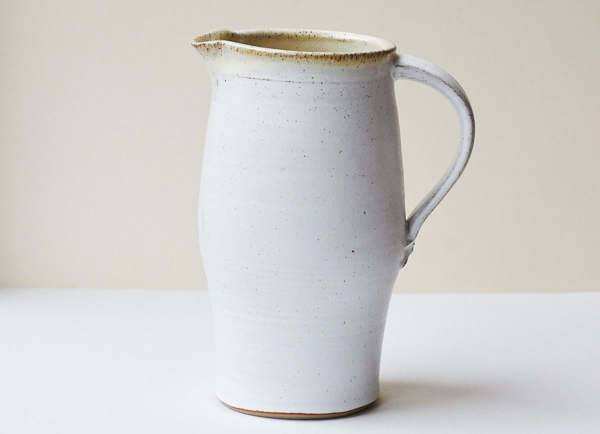 A white glazed stoneware water jug on a beige and white background