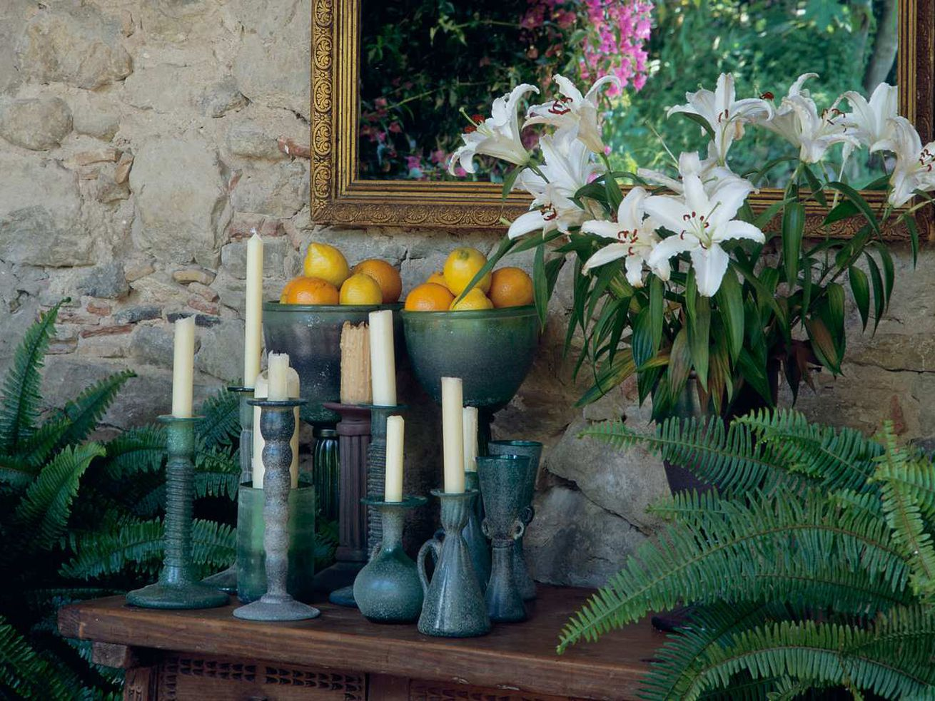 Blue candlestick holders with white candles on a wooden table, next to a vase of lilies.