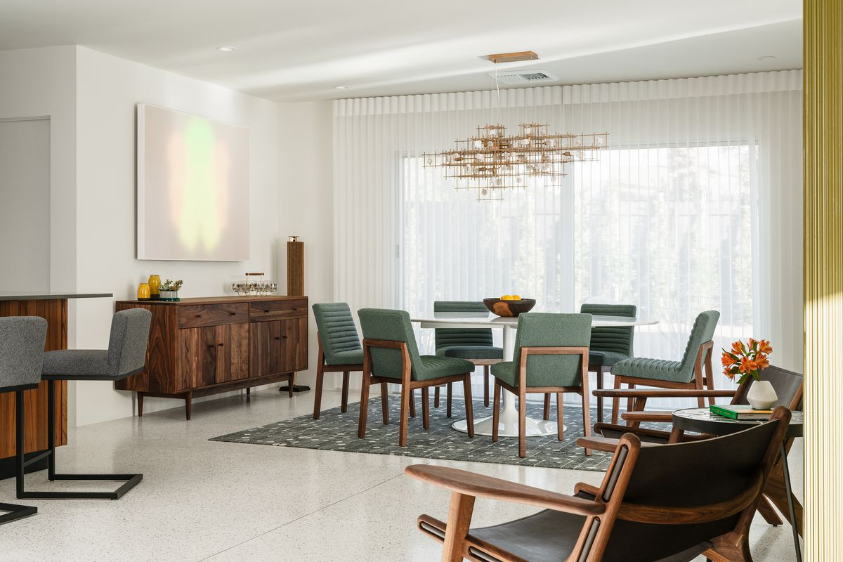 A dining room has a modern gold chandelier, seating for six, and a buffet table on the side.