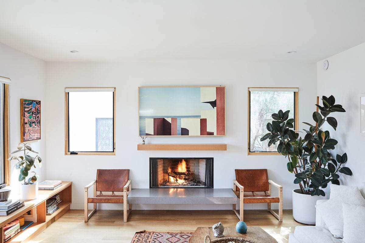 A bright and sunny living room, with a lit fire in the fireplace, two brown leather chairs on either side of the fireplace, and a blue and brown toned painting above. A large plant in a white planter is in one corner of the room, bookshelves with another small plant and books on the other side of the room.