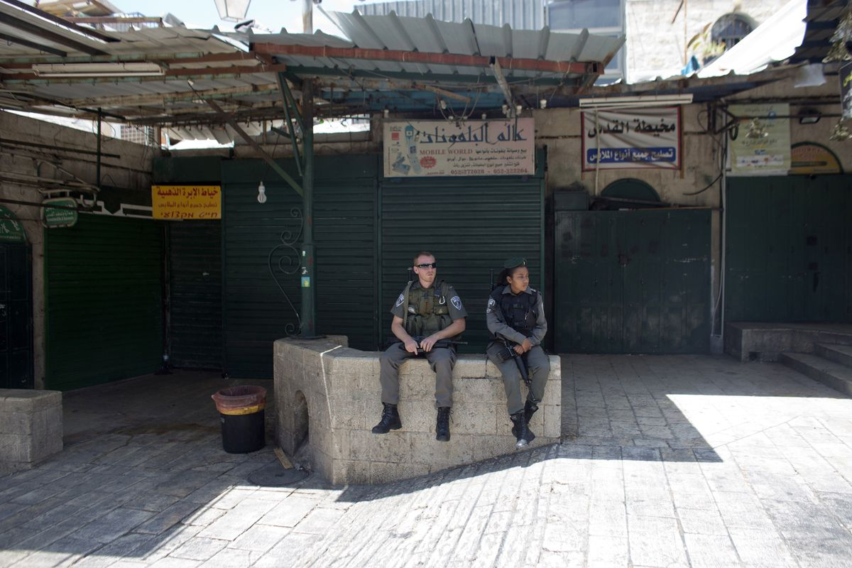 Israeli security forces sit in front of businesses in the Old City of Jerusalem that closed in solidarity with hunger-striking Palestinian prisoners.