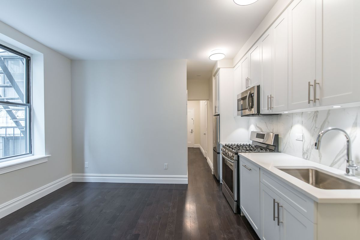 A small living area with a window and an open kitchen with white cabinetry.