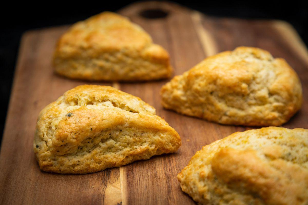Four crispy baked cheddar scallion scones sitting atop a wood cutting board