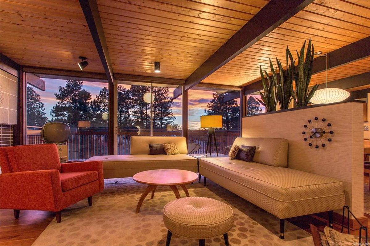 Interior shot of living room at dusk showing the sunset through sliding glass doors. The room features tounge-and-groove ceiling, exposed beams, fireplace, and sleek, cushioned furniture in neutral tones.