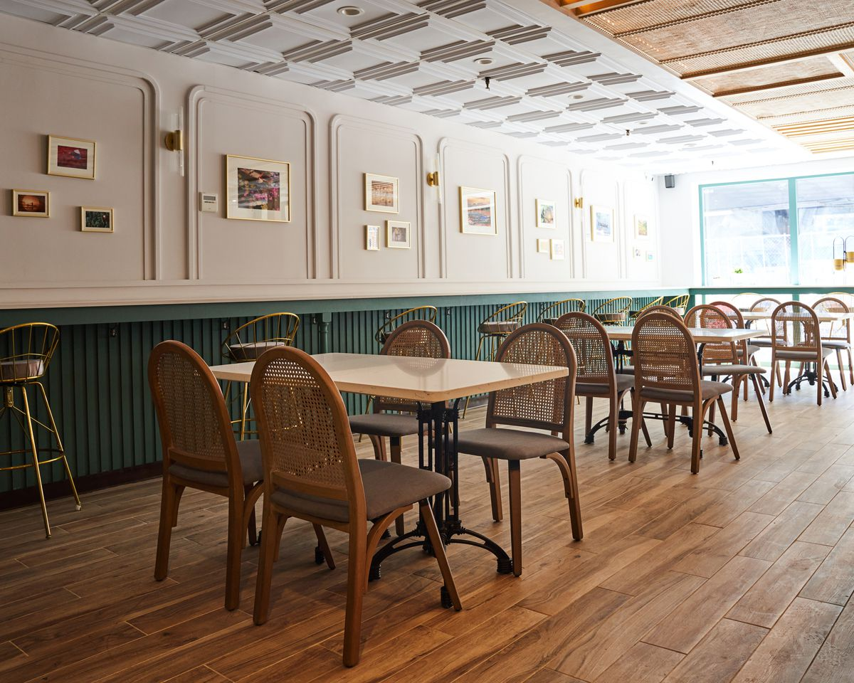 A naturally lit indoor dining room with wooden chairs, tables, and bar seating along one wall