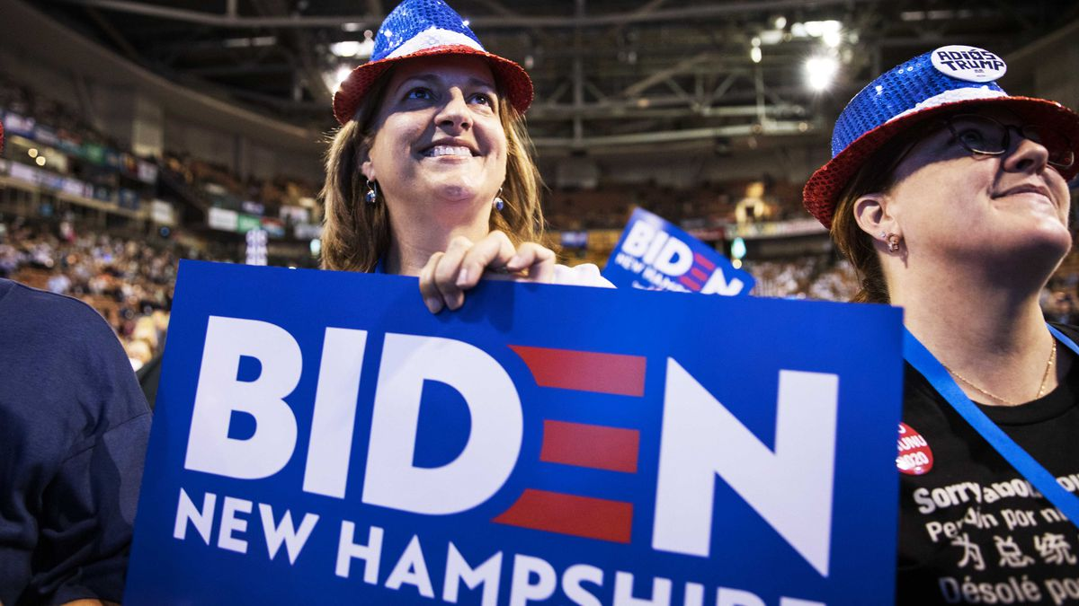 """A smiling woman holds a blue sign that reads """"Biden New Hampshire."""""""