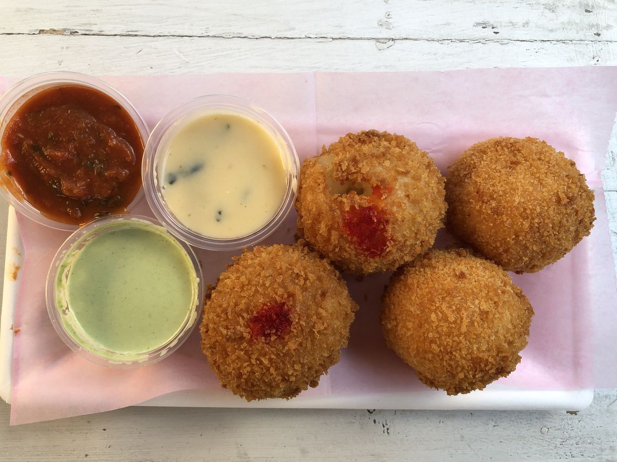 A plate of four rellenos — cheese and meat filled, golden brown deep fried balls placed on a tray with three sauces next to them