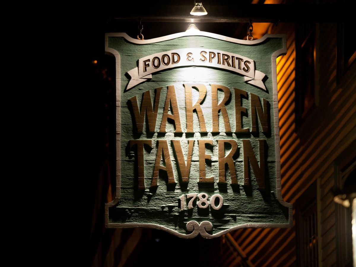 Light illuminates a sign for Warren Tavern, a Charlestown pub founded in 1780