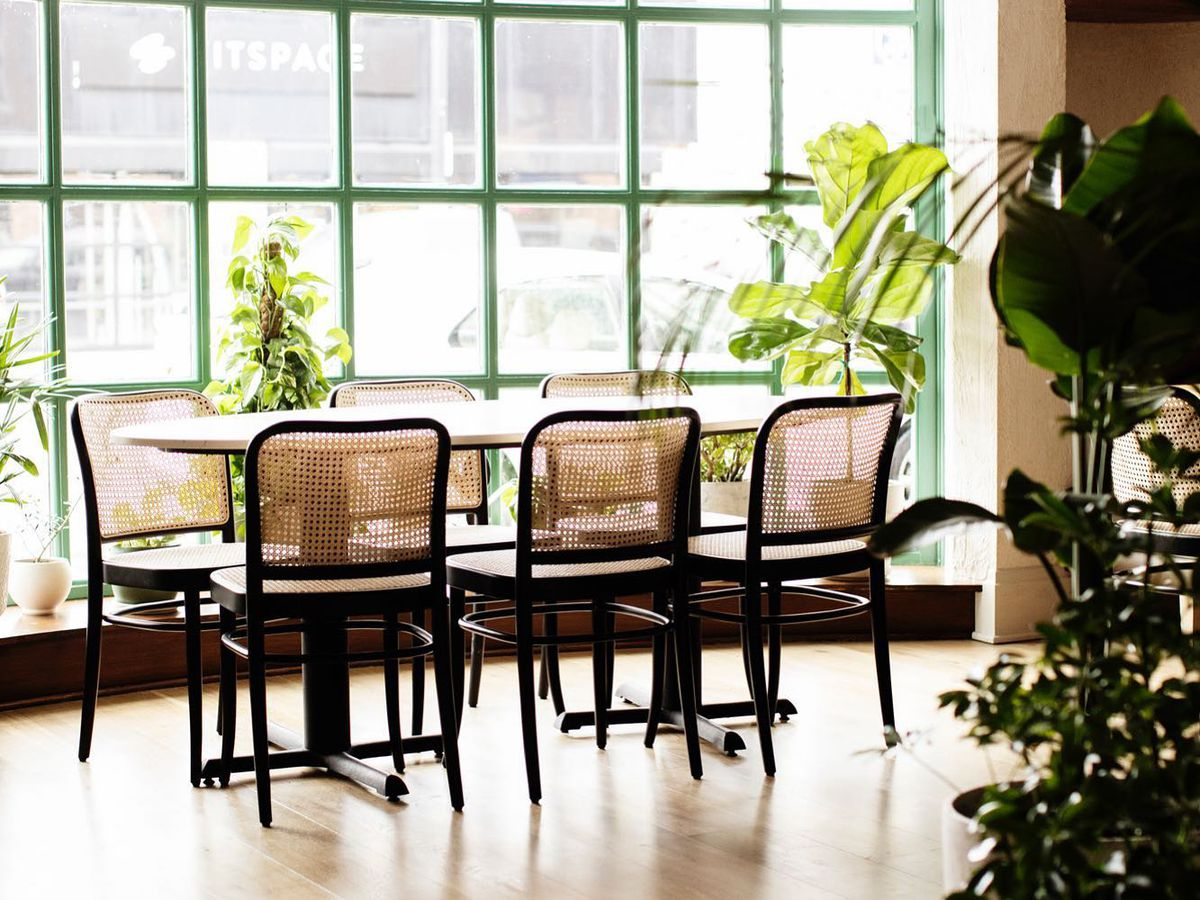 An oval table lined by wicker backed chairs in the front floor-to-ceiling windows, edged with a bright blue/green paint.