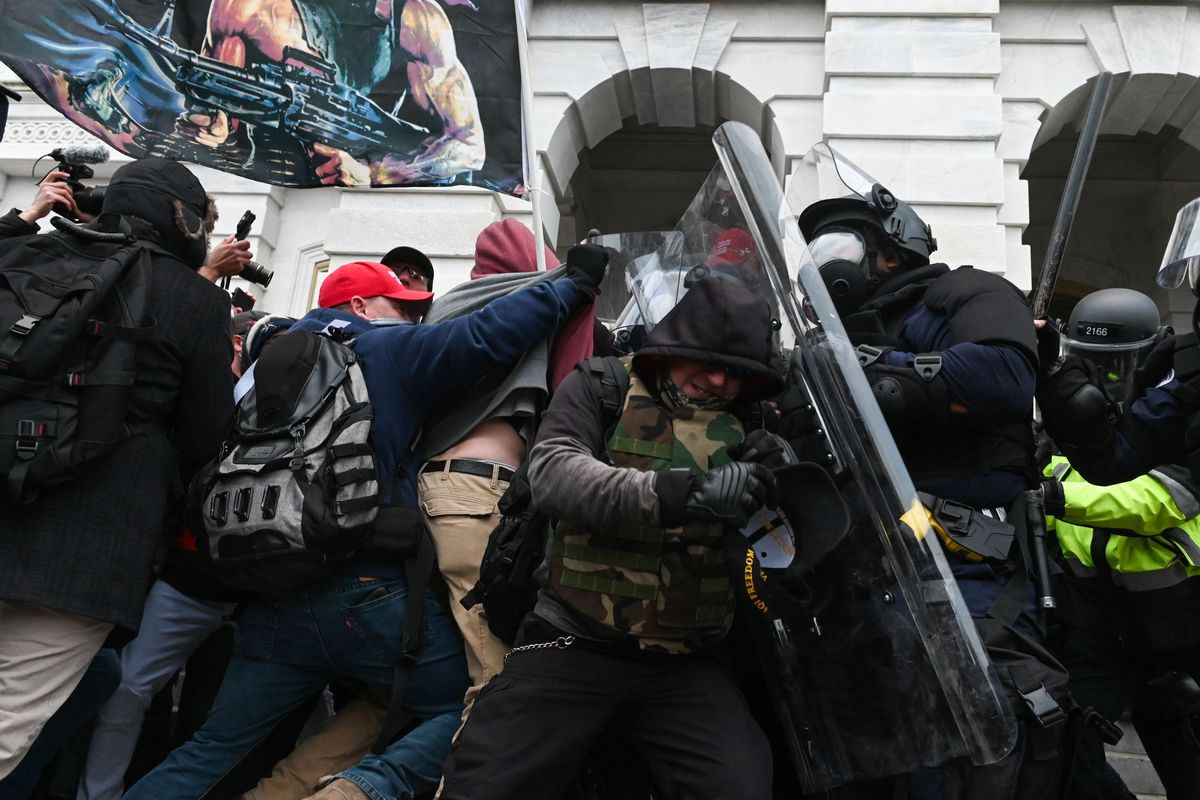 Rioters push against police shields outside the Capitol.