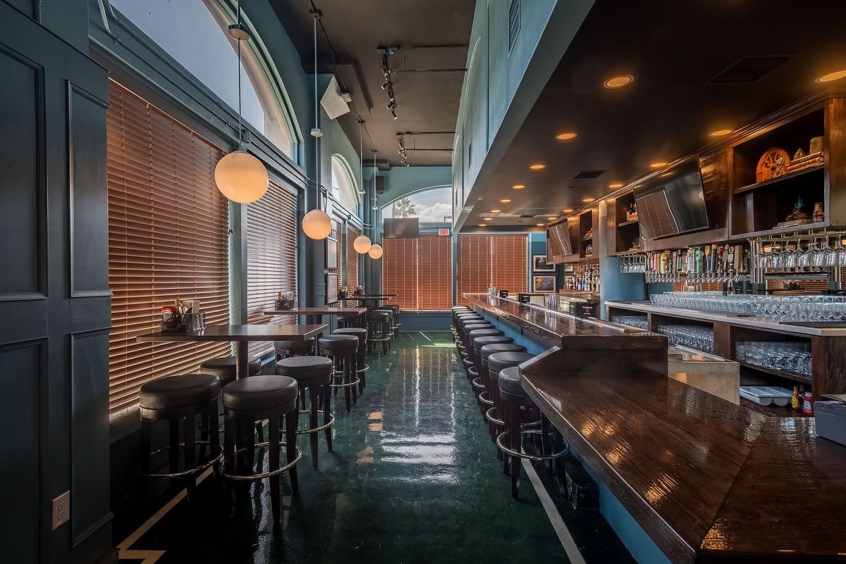 Inside The Greyhound Glendale with a bar, barstool, and covered windows with blinds and hanging lights.