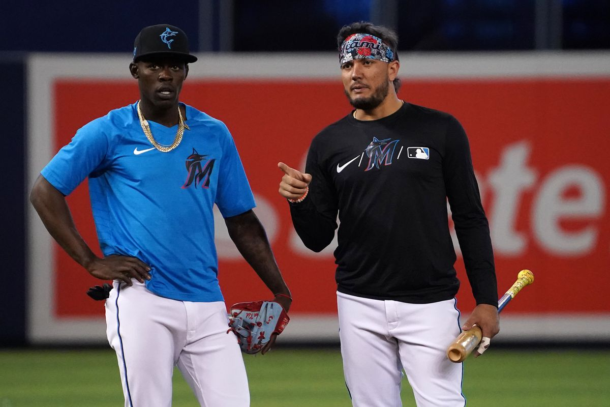 Miami Marlins shortstop Jazz Chisholm Jr. (L) talks with shortstop Miguel Rojas (R) prior to the game against the Atlanta Braves at loanDepot park