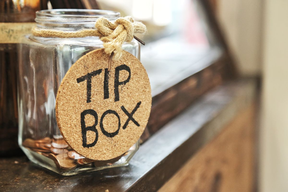 """A jar that says """"Tip Box"""" with a few coins at the bottom"""