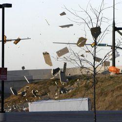 Debris from a construction site near the Farmington station of FrontRunner flies over the road Thursday, Dec. 1, 2011.