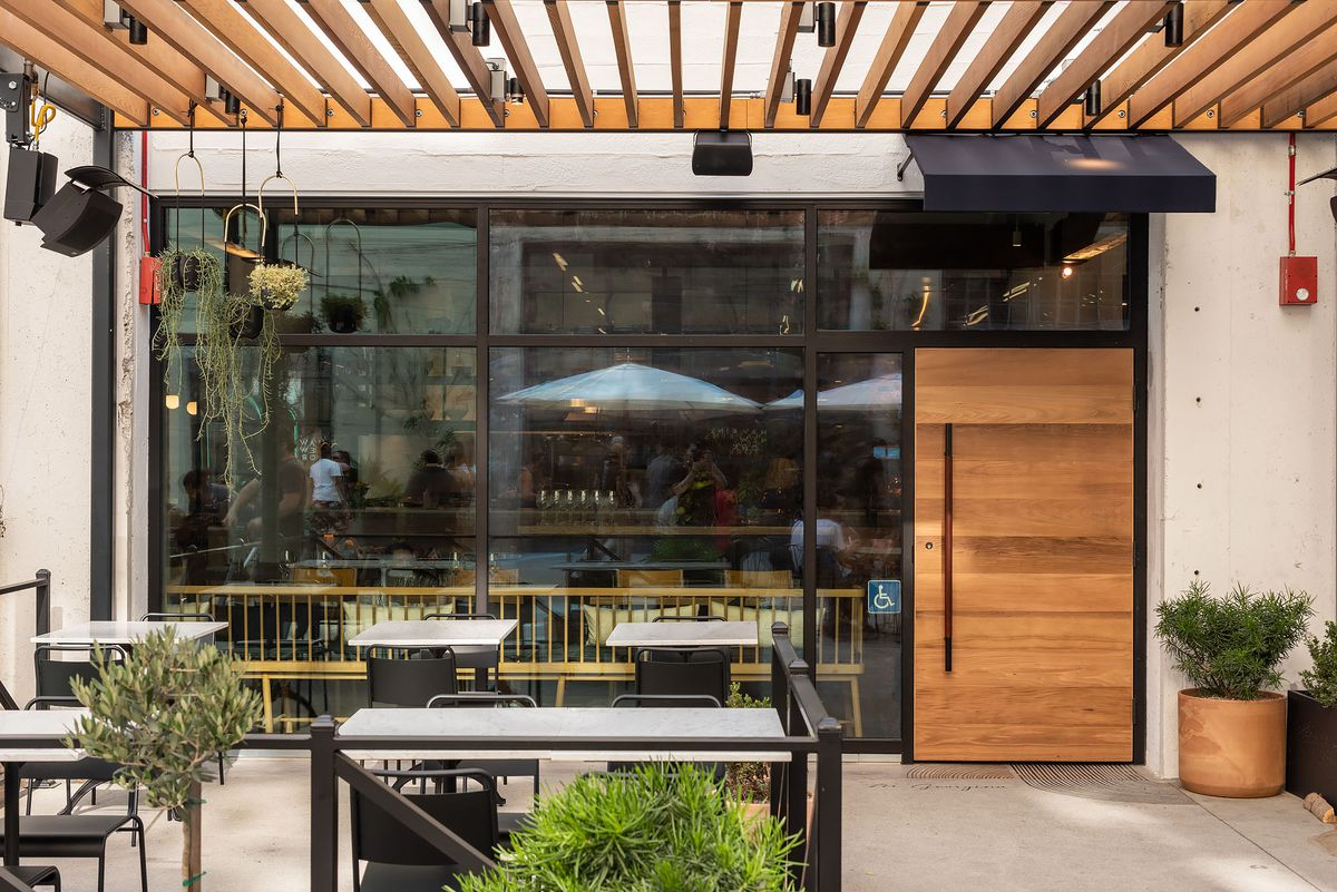 A small patio in front of a glassy new restaurant.
