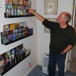 Outside his home recording studio, Kenny Hodges points to a shelf of audiobooks he has recorded and produced for Deseret Book and Shadow Mountain.
