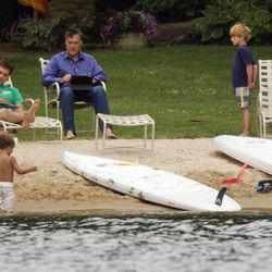 Republican presidential candidate, former Massachusetts Gov. Mitt Romney, right, with his laptop at hand, sits with his family by Lake Winnipesaukee Saturday, July 14, 2012, at his home in Wolfeboro, N.H.