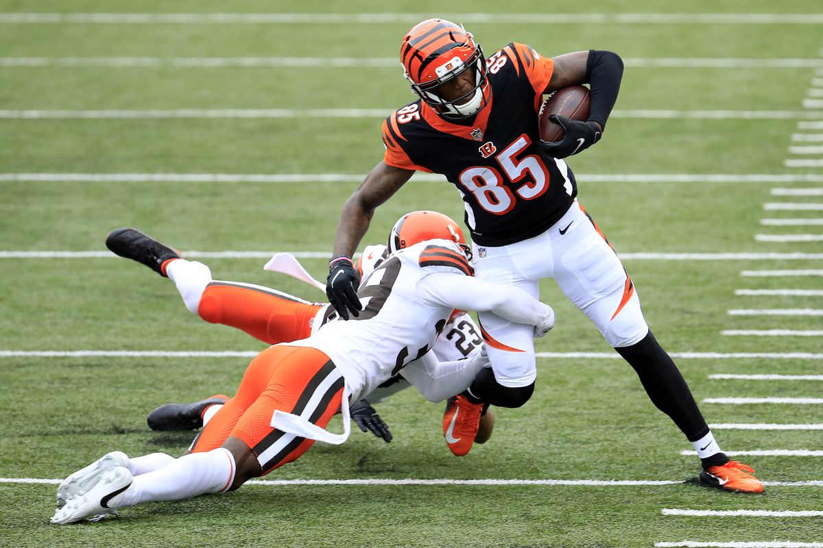 Tee Higgins #85 of the Cincinnati Bengals is tackled by Andrew Sendejo #23 and Terrance Mitchell #39 of the Cleveland Browns during the second half at Paul Brown Stadium on October 25, 2020 in Cincinnati, Ohio.