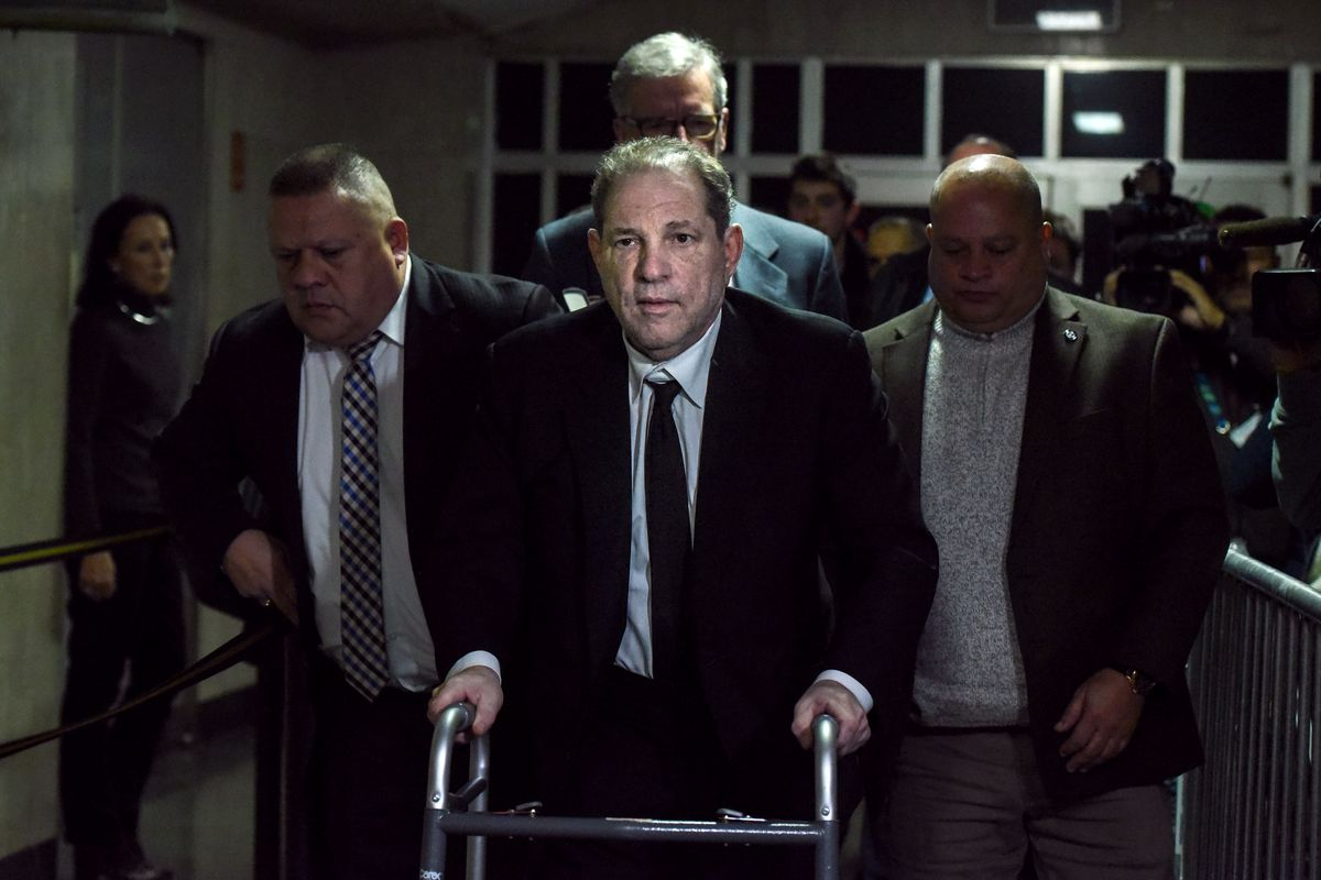 Harvey Weinstein, using a walker, leaves court flanked by other people.