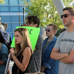 Abby Stover, left, and Jake Macfarlane listen to speakers during a rally in Salt Lake City on Saturday, Sept. 2, 2017. Nearly 100 people gathered in Salt Lake City at a rally protesting police conduct against a University Hospital nurse who refused to allow a blood draw from an unconscious patient.