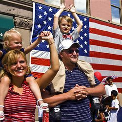 Angela Olsen and her husband, Jared, with their children Anya, 2, and Dylan, 5, enjoy Saturday's parade in Provo.