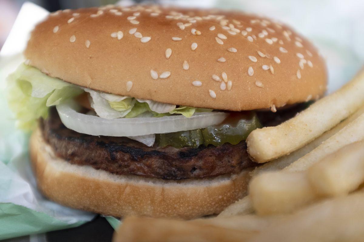 A hamburger on a bun beside a pile of fries.
